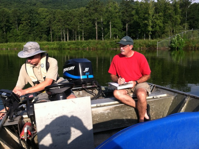 John Damer and Noel Holcomb record data from lake survey work on Lake Marvin.